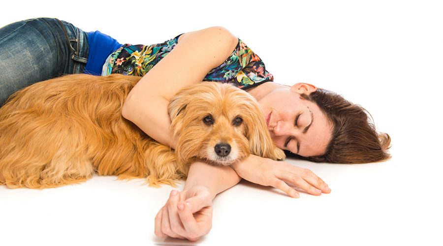 A young woman cuddles with her pet dog